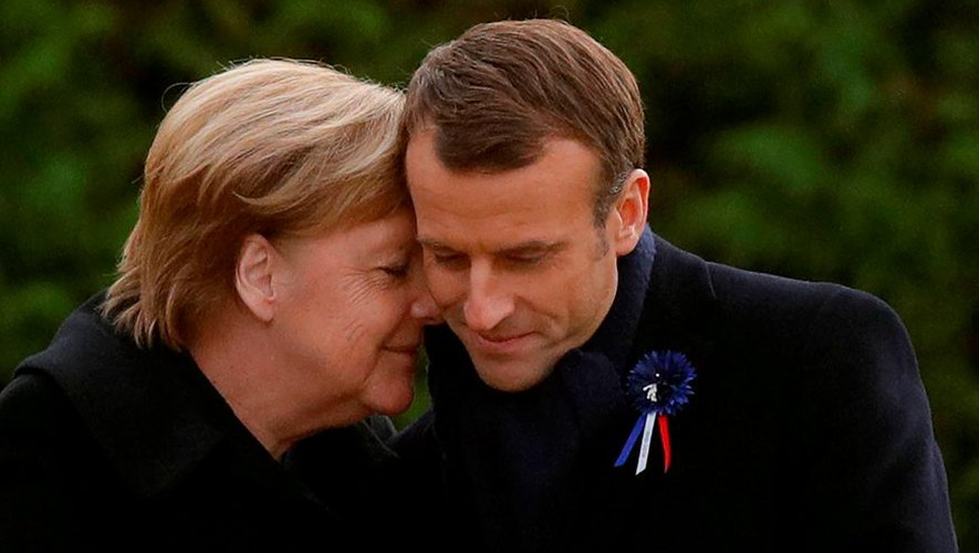 TOPSHOT - French President Emmanuel Macron and German Chancellor Angela Merkel hug after unveiling a plaque in a French-German ceremony in the clearing of Rethondes (the Glade of the Armistice) in Compiegne, northern France, on November 10, 2018 as part of commemorations marking the 100th anniversary of the 11 November 1918 armistice, ending World War I. (Photo by PHILIPPE WOJAZER / POOL / AFP) TOPSHOT-FRANCE-WWI-POLITICS-HISTORY-CENTENARY